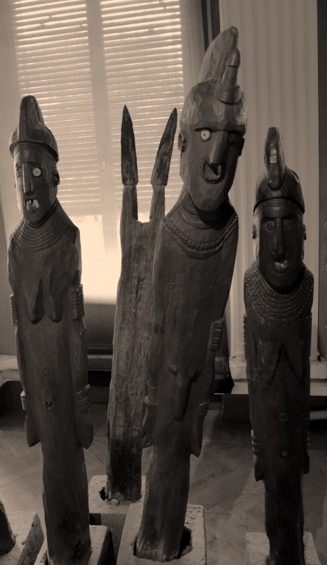 Photo by Suzi Richer. A few characters from the waka on display in the Ethnographic Museum. Left to right: second wife of the 'hero', 'hero', first wife of the 'hero', the shield on spears of the 'hero' are depicted behind them. 'Hero' was the term used in the display depiction.